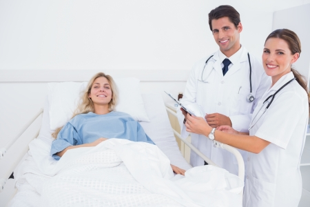 Smiling patient and doctors in a bedroom photo