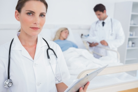 serious doctor: Serious doctor holding folder in front of a patient and a doctor