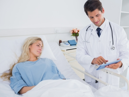 Doctor showing digital tablet to patient photo