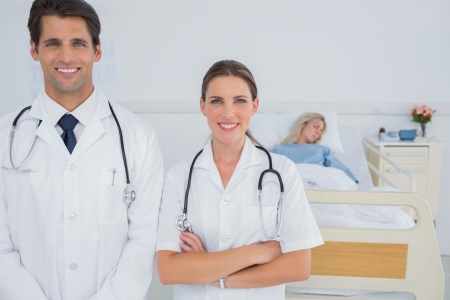 Two doctors smiling and standing in front of a hospitalized patient Stock Photo - 20586423