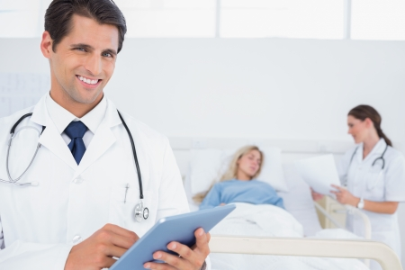 Handsome doctor using digital tablet in front of patient and doctor photo