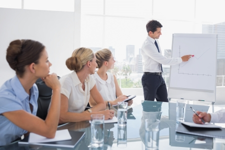 sala de reuniones: Hombre de negocios que se�ala en una carta cada vez mayor en una reuni�n