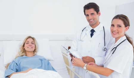 Smiling doctors standing next to a hospitalized patient photo