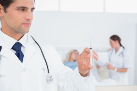 Handsome doctor holding syringe in front of patient photo