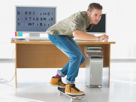 Handsome employee skating through the office and having fun photo