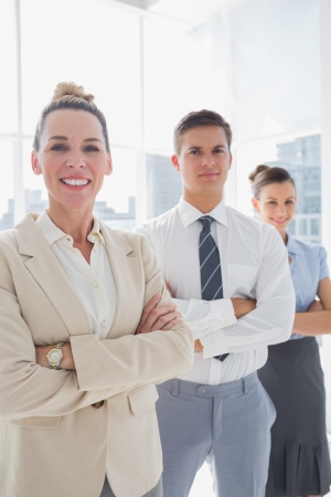 Smiling attractive businesswoman standing with arms folded in front of colleagues photo