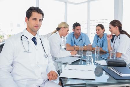 equipe medica: Medico sorridendo alla telecamera mentre il suo team lavora