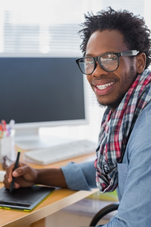 graphic designing: Cheerful graphic designer using a graphics tablet in a modern office Stock Photo