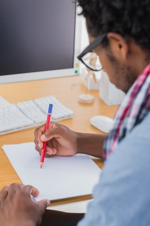 Creative business worker with reading glasses drawing something in a modern office Stock Photo