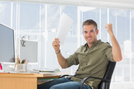 Creative business employee raising arms in a modern office photo