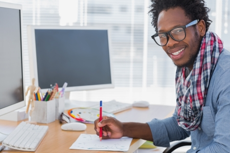 Smiling designer drawing something with a red pencil in a modern office photo