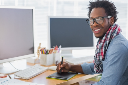 designing: Smiling graphic designer using a graphics tablet in a modern office Stock Photo