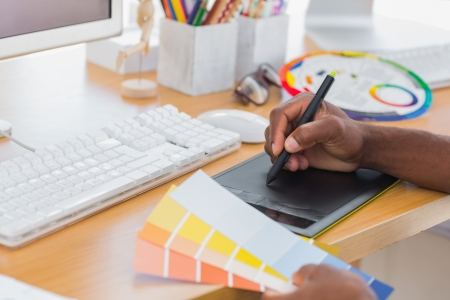 graphics tablet: Designer using graphics tablet while holding colour charts