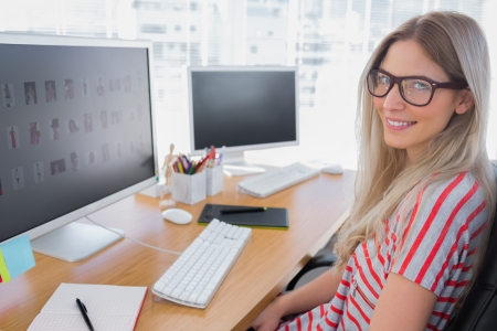 graficos: Editor de fotos atractiva que trabaja en el ordenador en una oficina moderna Foto de archivo