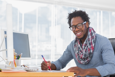 Smiling designer drawing with a red pencil on a desk in a modern office photo