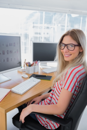 editor: Portrait of a smiling photo editor in a modern office
