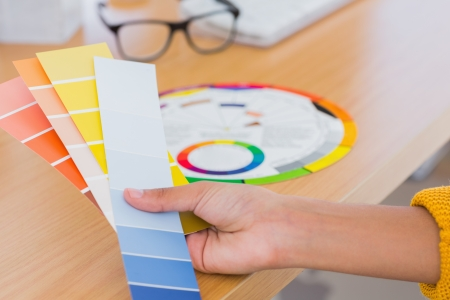 Hand holding colour swatches over a desk with colour wheel photo