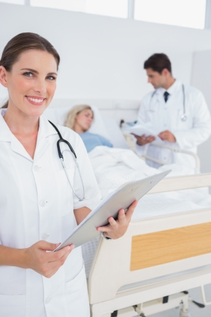 Smiling doctor holding folder in front of a patient and a doctor photo