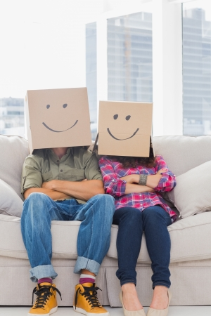 Funny workers with arms folded wearing boxes on their heads with smiley faces on a couch photo