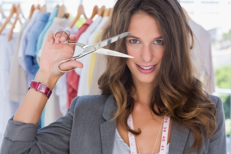 Attractive designer holding scissors in front of her face photo