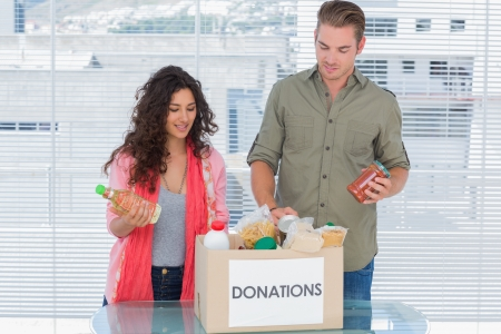 Volunteers taking out food from donations box for a charity photo