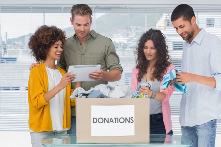 Volunteers using tablet and taking out clothes from a donation box for a charity photo