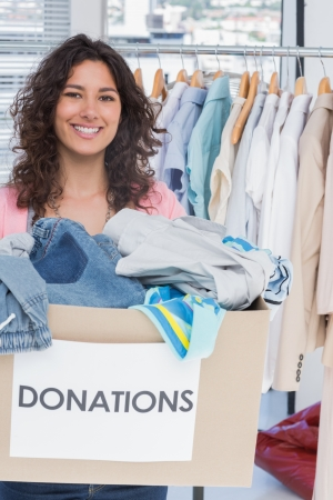 give charity: Woman volunteer smiling and holding donation box Stock Photo