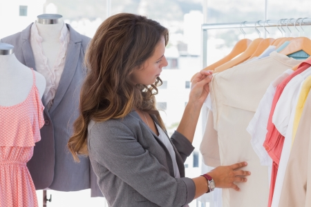 clothes rail: Fashion designer looking at clothes rail in her studio