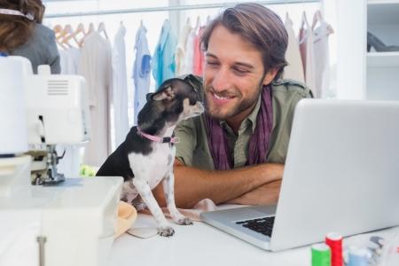 Cute chihuahua sitting on desk next to a fashion designer photo
