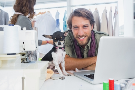 Smiling fashion designer with his chihuahua sits on desk photo
