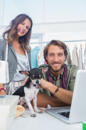 Two fashion designers smiling to the camera with a chihuahua photo