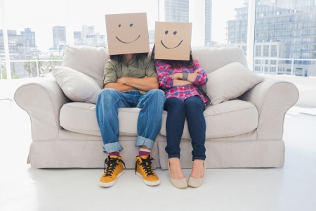 Silly employees with arms folded wearing boxes on their heads with smiley faces on a couch photo