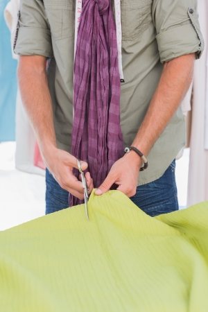 Fashion designer cutting green textile with scissors photo