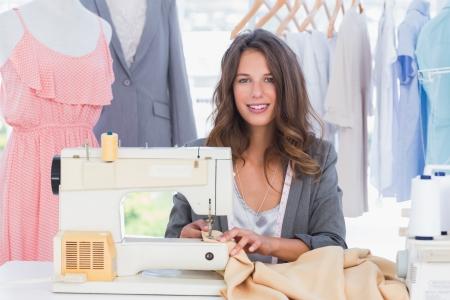 maquina de coser: Dise�ador de moda sonriente que usa la m�quina de coser y se sienta detr�s de su escritorio Foto de archivo