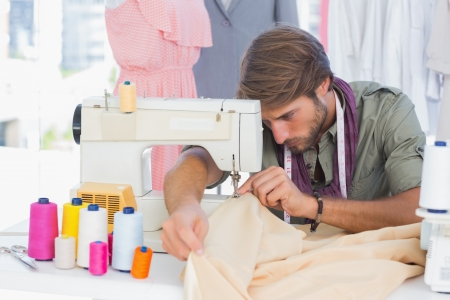 office machine: Handsome fashion designer sewing with a sewing machine
