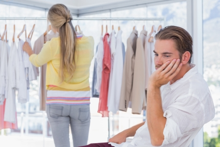 Bored man while his girlfriend is shopping in a boutique Stock Photo - 20591555