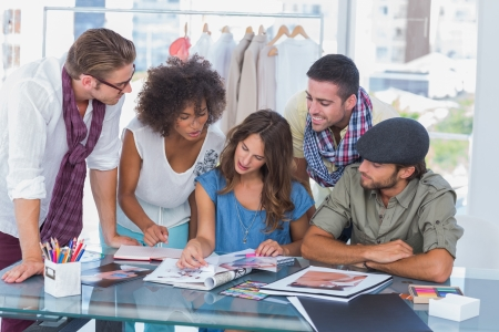 Young designers looking at photos in office at desk photo
