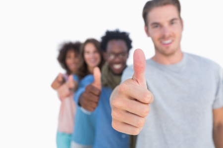 Young people in row with thumbs up against white background