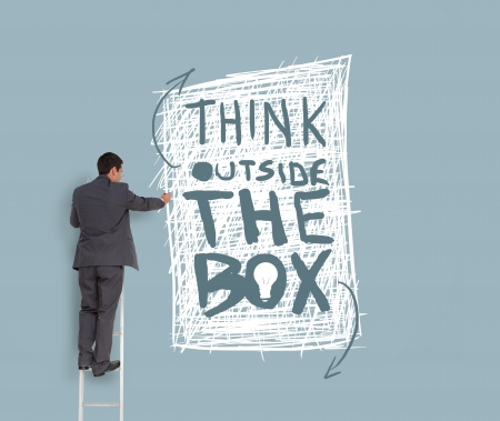 individualism: Businessman drawing think outside the box message on grey wall