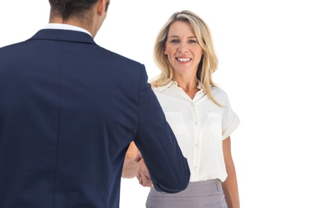 agreeing: Smiling businesswoman shaking hands and looking at the camera Stock Photo