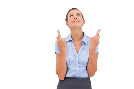 fingers crossed: Wishing businesswoman with fingers crossed looking to the sky