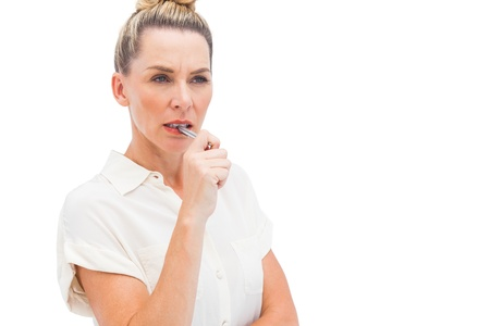 Focused businesswoman with pen on mouth looking at the camera Stock Photo - 20539380
