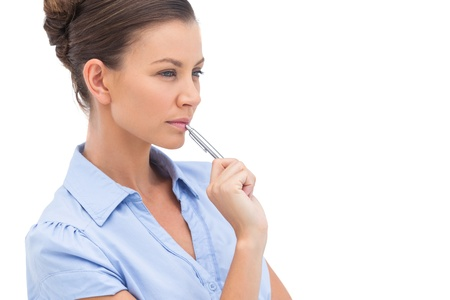 Concentrating businesswoman with pen looking away Stock Photo - 20539666