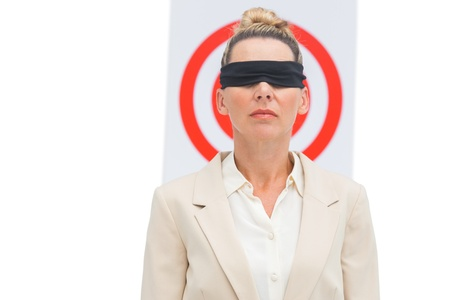 Businesswoman blindfolded and target behind her photo