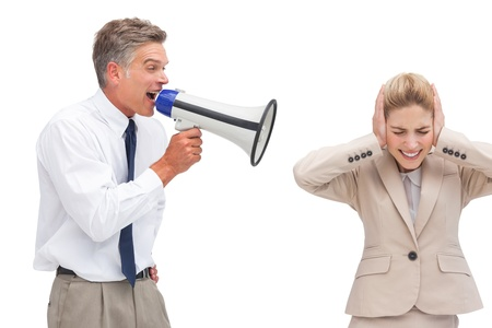 Mature businessman shouting at his coworker with megaphone on white background photo