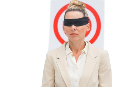 Businesswoman blindfolded in front of red target photo