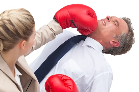 A businesswoman boxing her co worker on white background photo