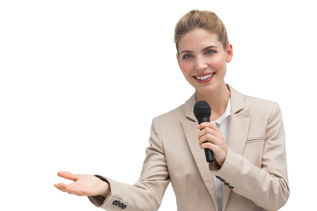 Businesswoman holding microphone and smiling at the camera photo
