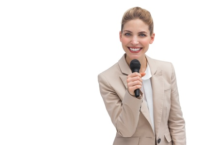 Smiling businesswoman holding microphone on white background photo