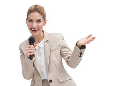 A gesturing businesswoman speaking on microphone with hand raised photo